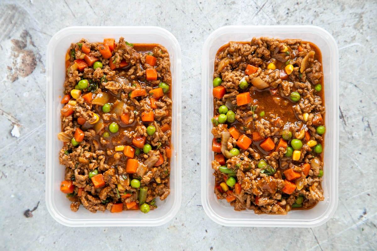 Two trays of savoury mince in shallow take away trays, ready to freeze.