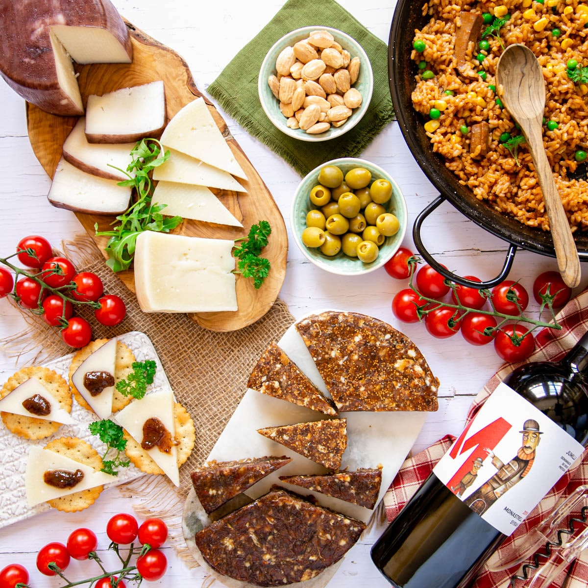 Top down of prepared food products from Murcia - sliced cheese, prepared paella, wine, nuts, olives, sliced dried fruit cakes.
