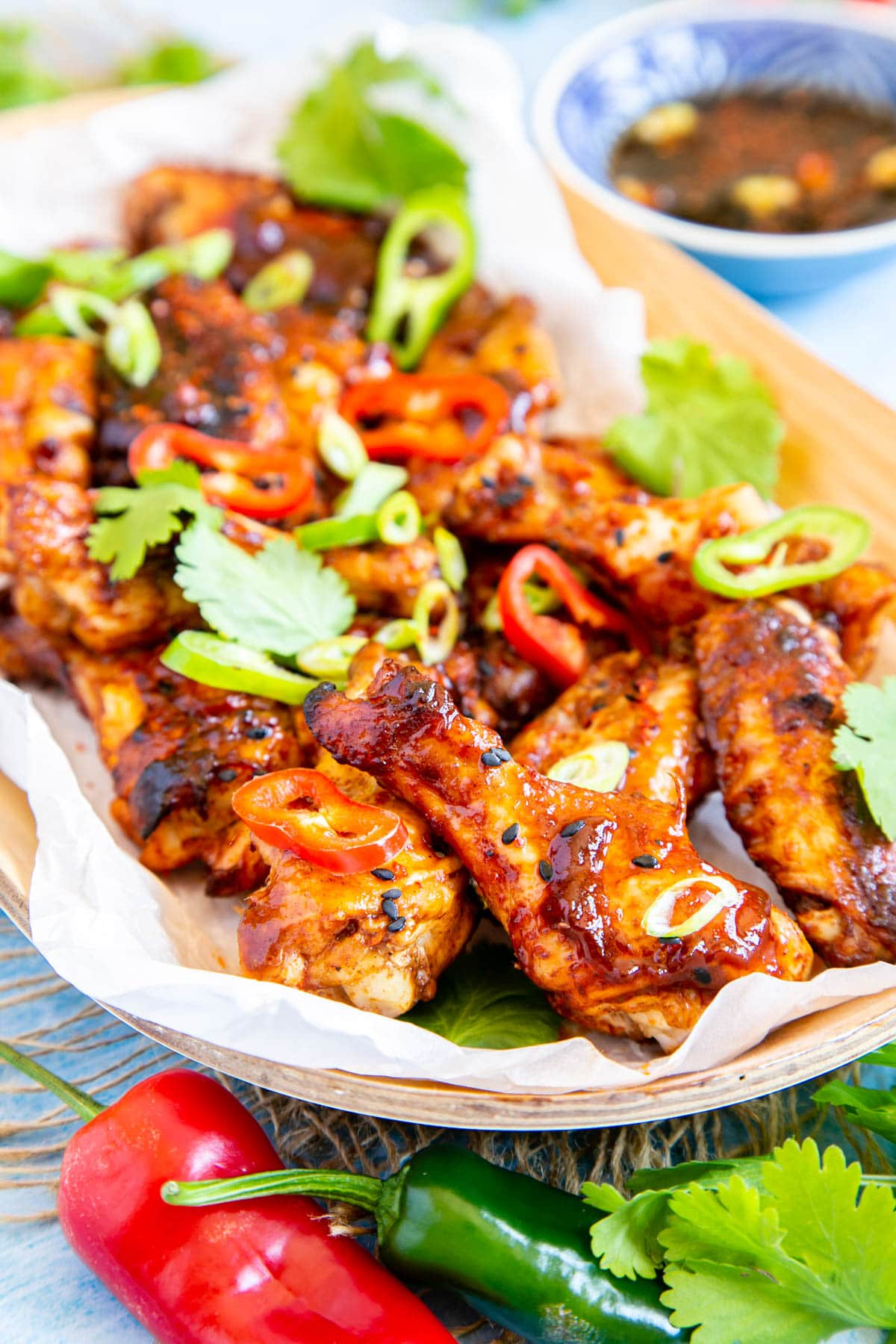 A close up of an oval wooden dish lined with greaseproof paper, full of sticky Asian chicken wings. The dish is garnished with sliced chillies and coriander leaves.