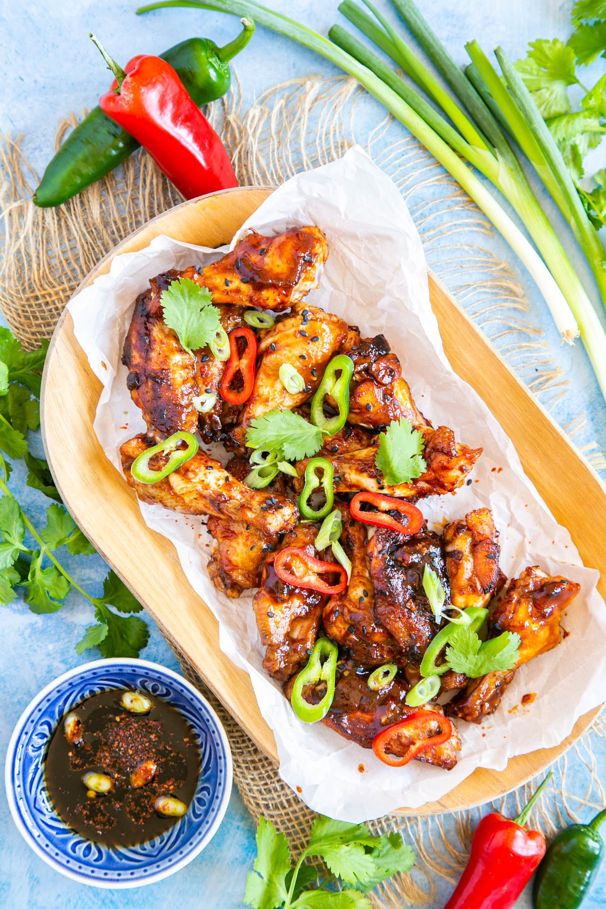 A top down picture of sticky Asian chicken wings. Next to the dish are whole chillies, and a small dish of more marinade/dipping sauce.