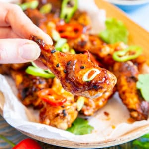 A hand picks up a wing, with the rest of the dish in the background.