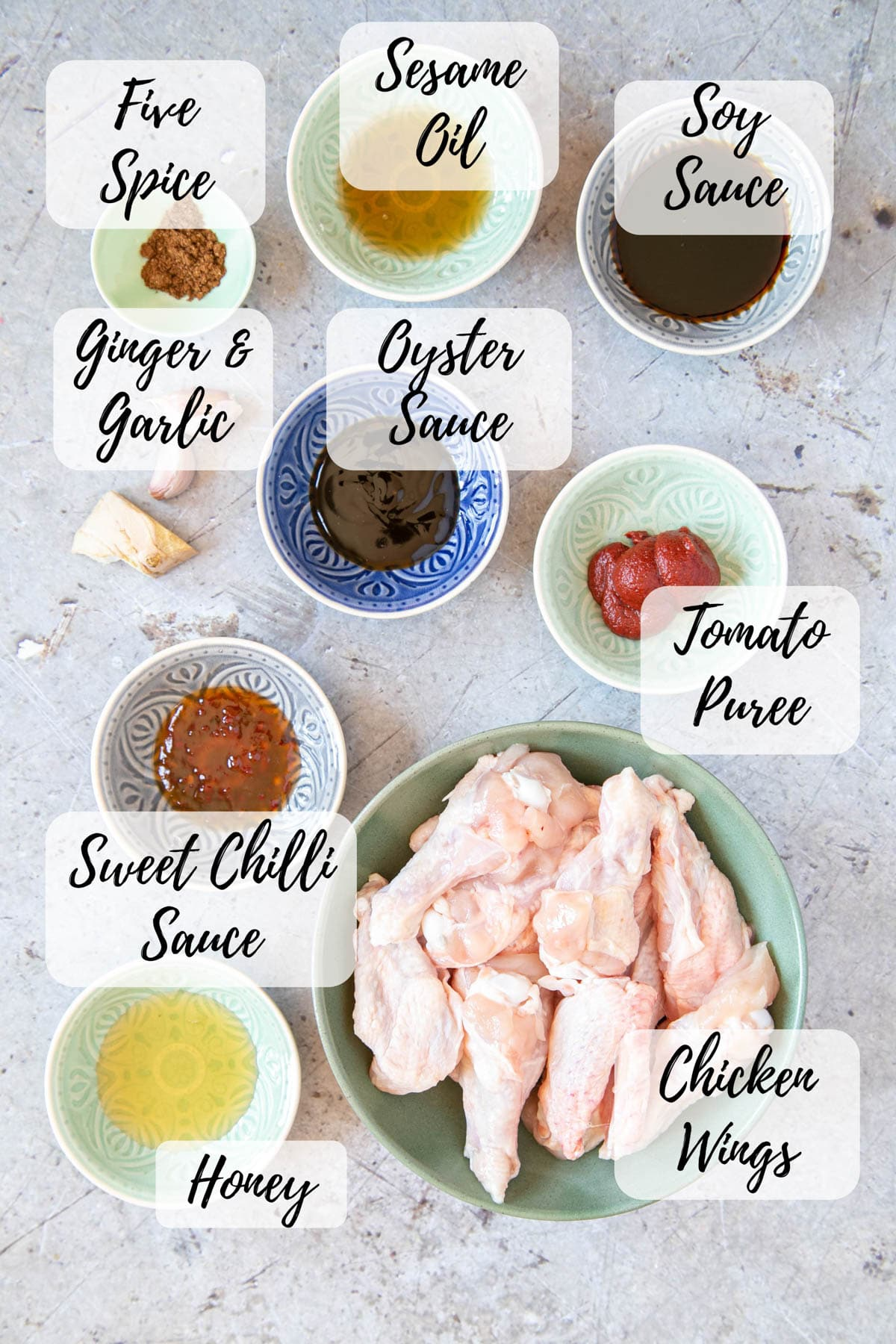The ingredients for sticky Asian chicken wings: chicken, tomato paste, sweet chilli sauce, honey, ginger, garlic, oyster sauce, soy sauce, sesame oil, and fie spice.