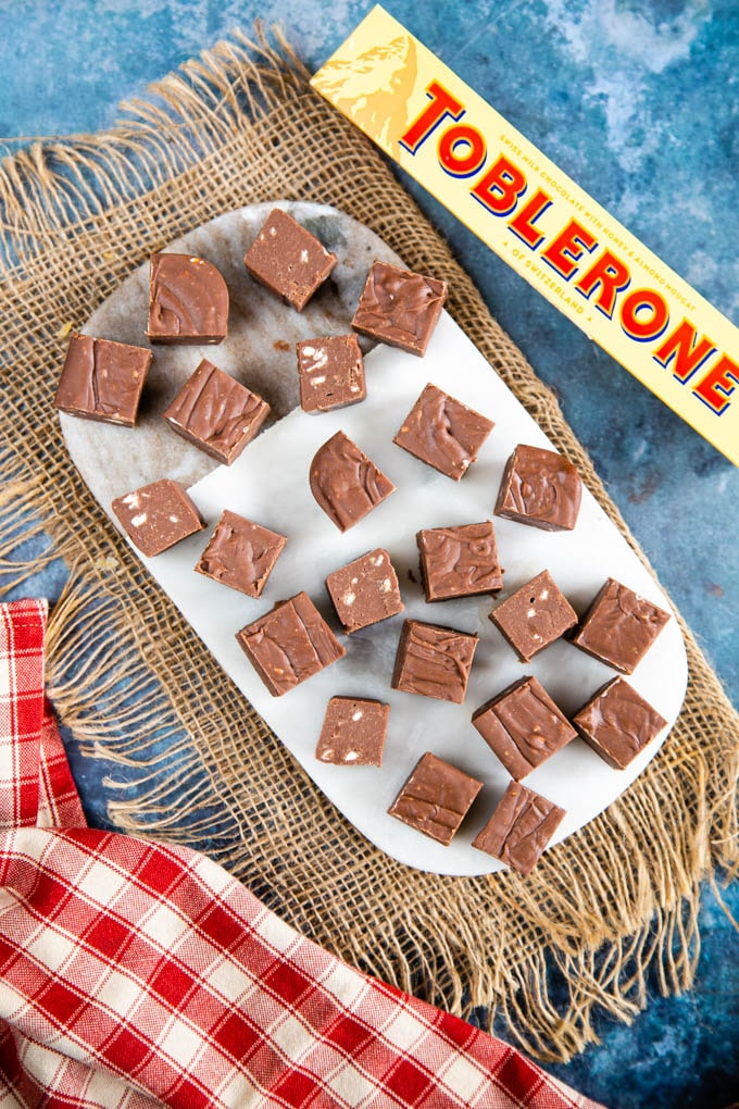 Pieces of fudge covering a marble board, which in its turn is sitting on a burlap cloth. A packet of Toblerone is next to the board.