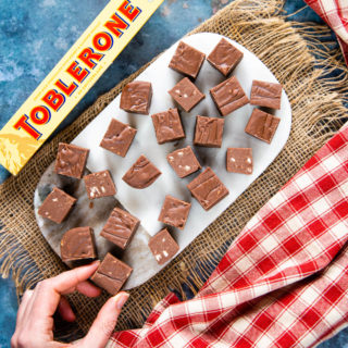 Top down picture of a marble board evenly covered with pieces of fudge. In the bottom left corner, a hand is taking a piece of fudge.