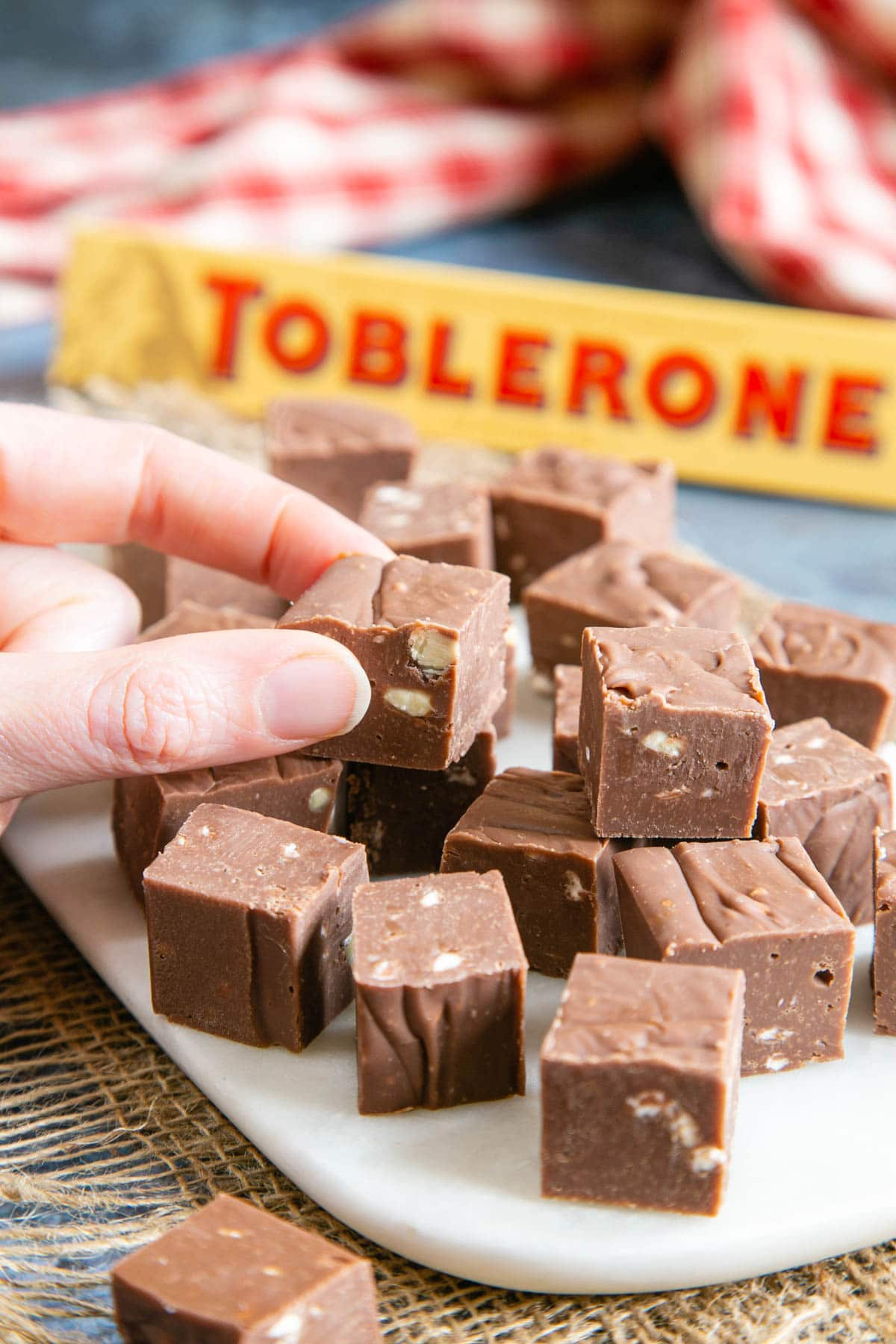 A picture of a hand taking a piece of fudge from a pile of 2cm cubes of fudge.