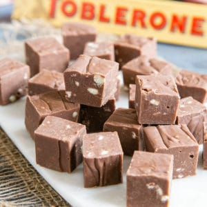 Toblerone fudge cubes arranged on a porcelain board. A packet of Toblerone in the background.