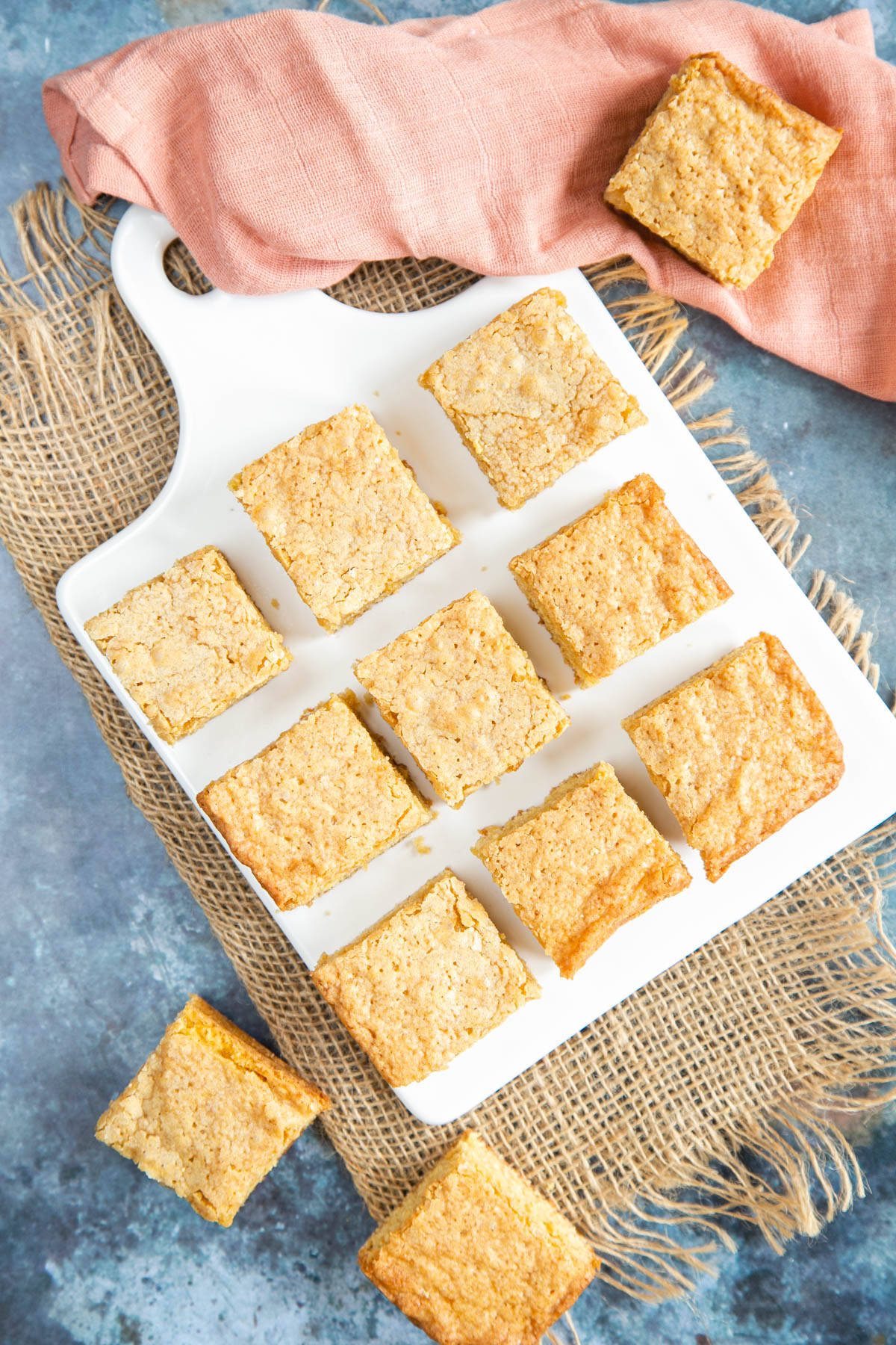 Top down picture of 9 vanilla tray bake squares arranged evenly in a square on a white porcelain board.