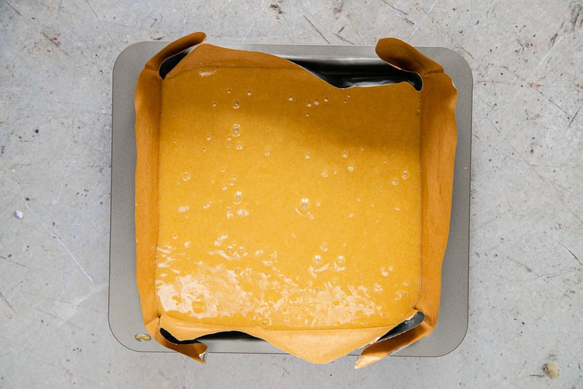 The batter for vanilla cake bars has been poured into a lined square cake tin.