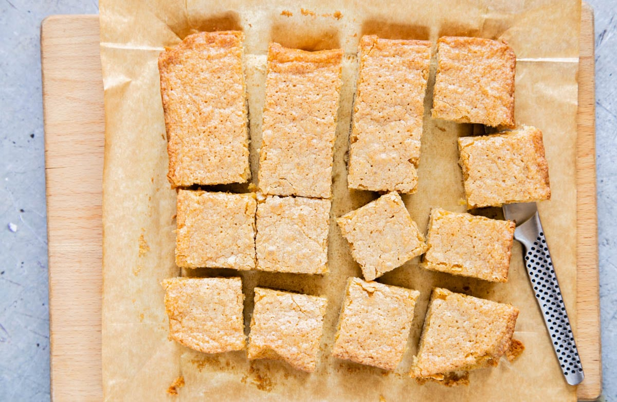 The vanilla tray bake has cooled and is being cut into 16 squares.