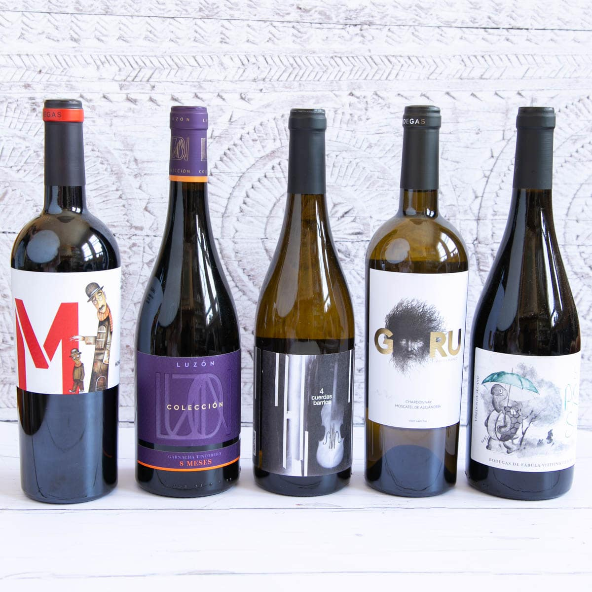 Five bottles of wine from Murcia, lined up in a row. Three red and two white wines, each with a stylish label.