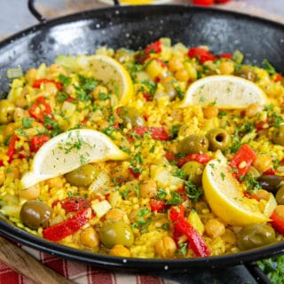 Close up of golden yellow paella showing lemon wedges, olives, and sliced peppers.