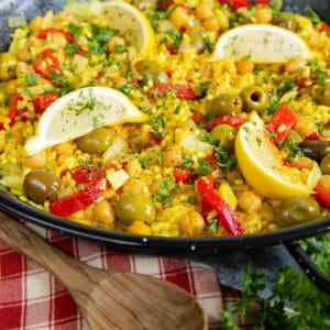 Close up of golden yellow paella with olives, chickpeas, and slices of red peppers.
