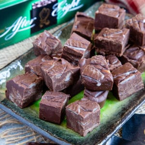 Close up of After Eight fudge pieces stacked up two high on a rectangular green and black plate.