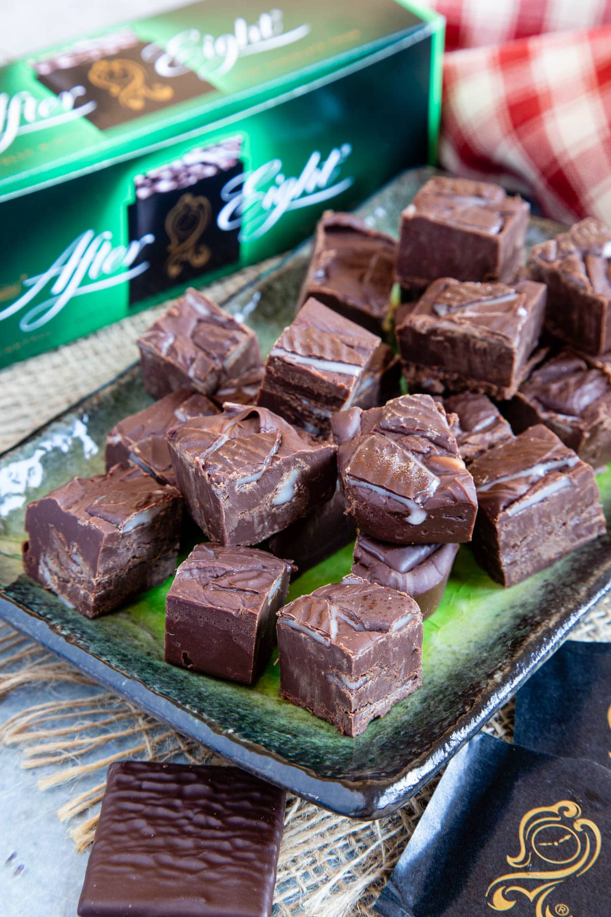 Close up of After Eight fudge pieces stacked up two high on a rectangular green and black plate. A mint and wrapper in the foreground, and box of mints in the background.