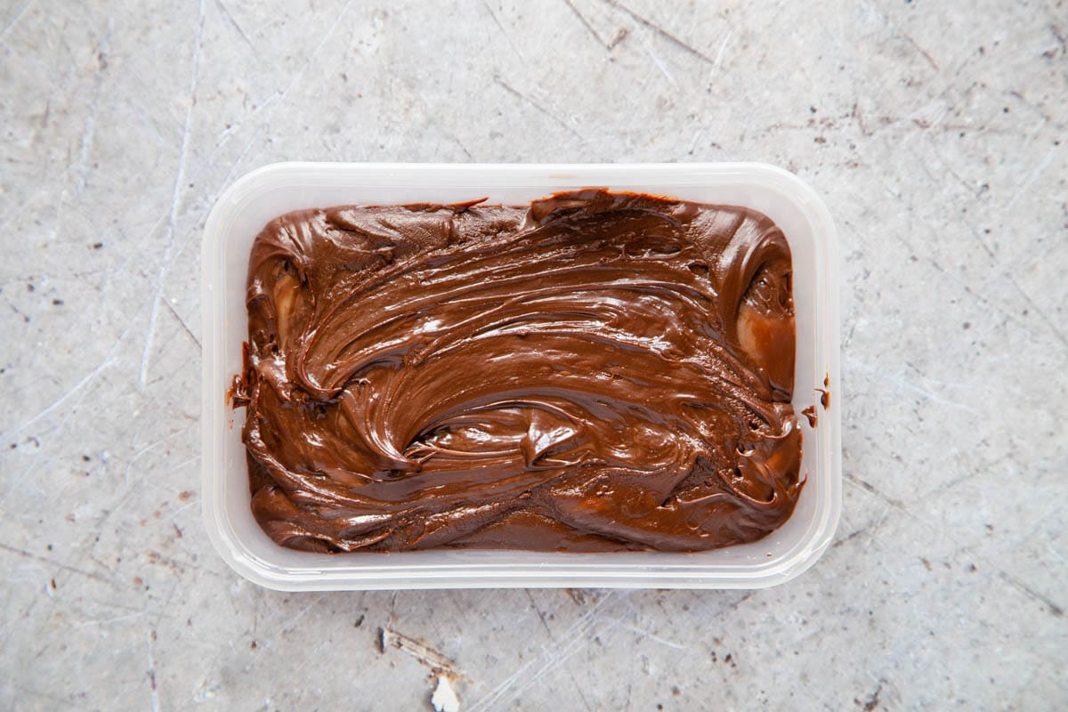 The fudge mixture has been spread evenly in a plastic box, ready to be chilled.