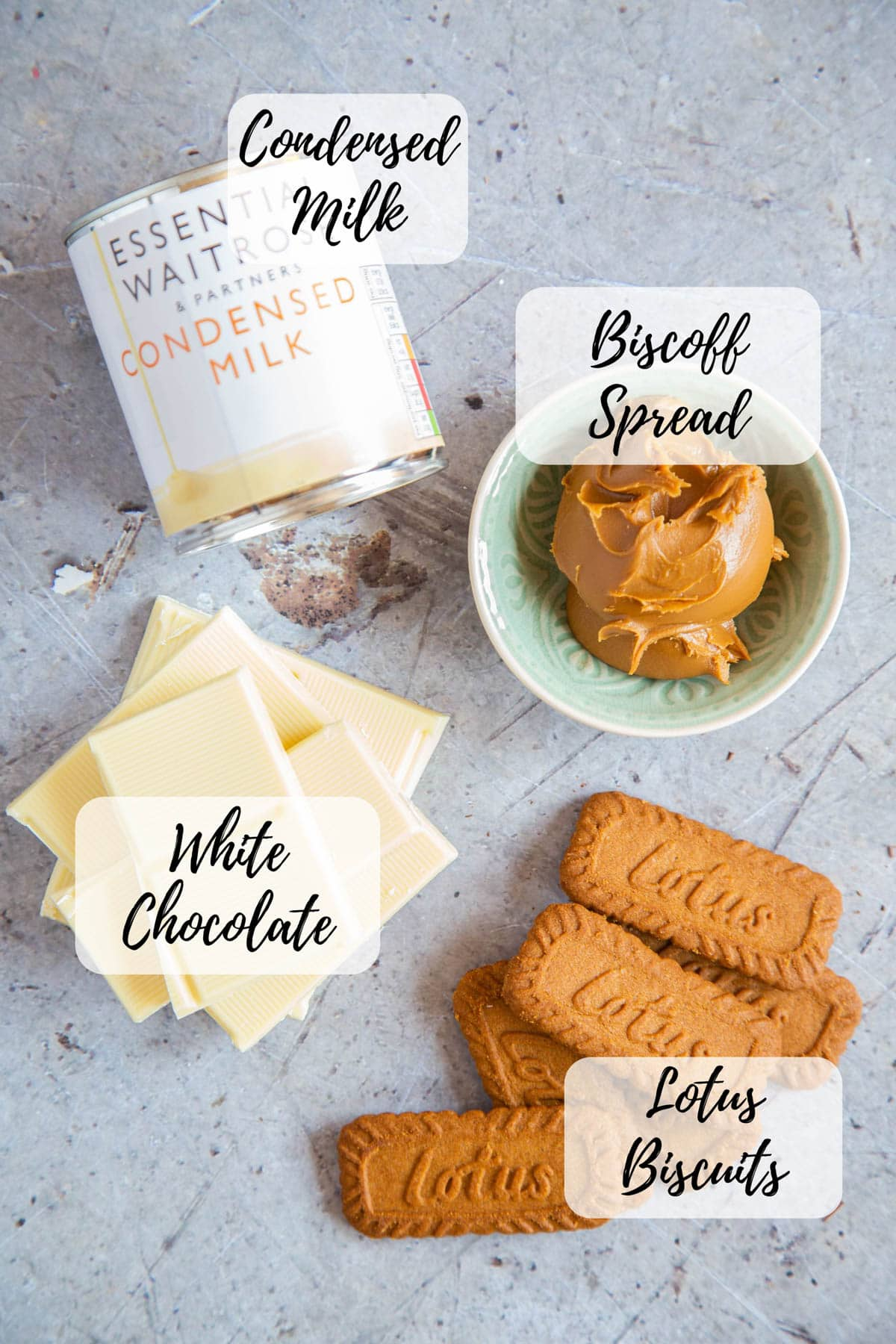 Ingredients for Biscoff fudge - condensed milk, biscoff spread, lotus biscuits, and white chocolate.