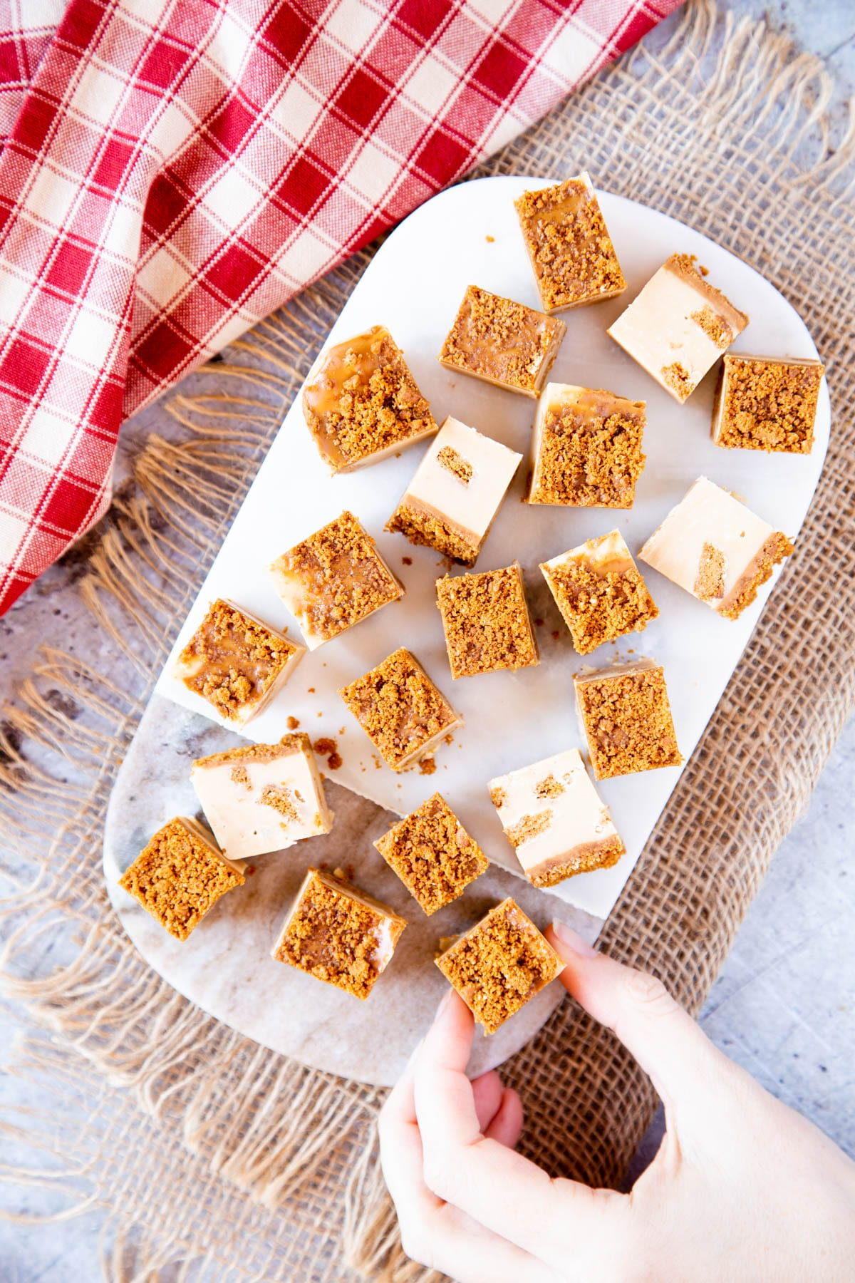 From above, delicious bite-sized pieces of Speculoos fudge arranged on a marble board. A hand is reaching in to take one piece.