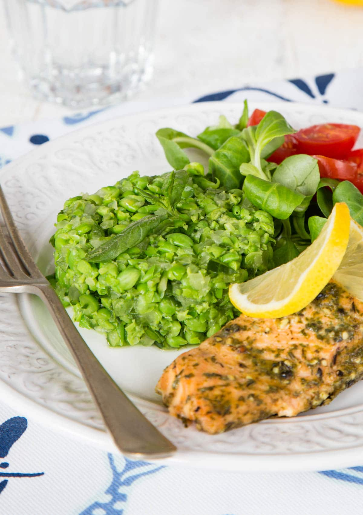 Deliciously vibrant green crushed minted peas, served on a white plate with some hot smoked salmon.