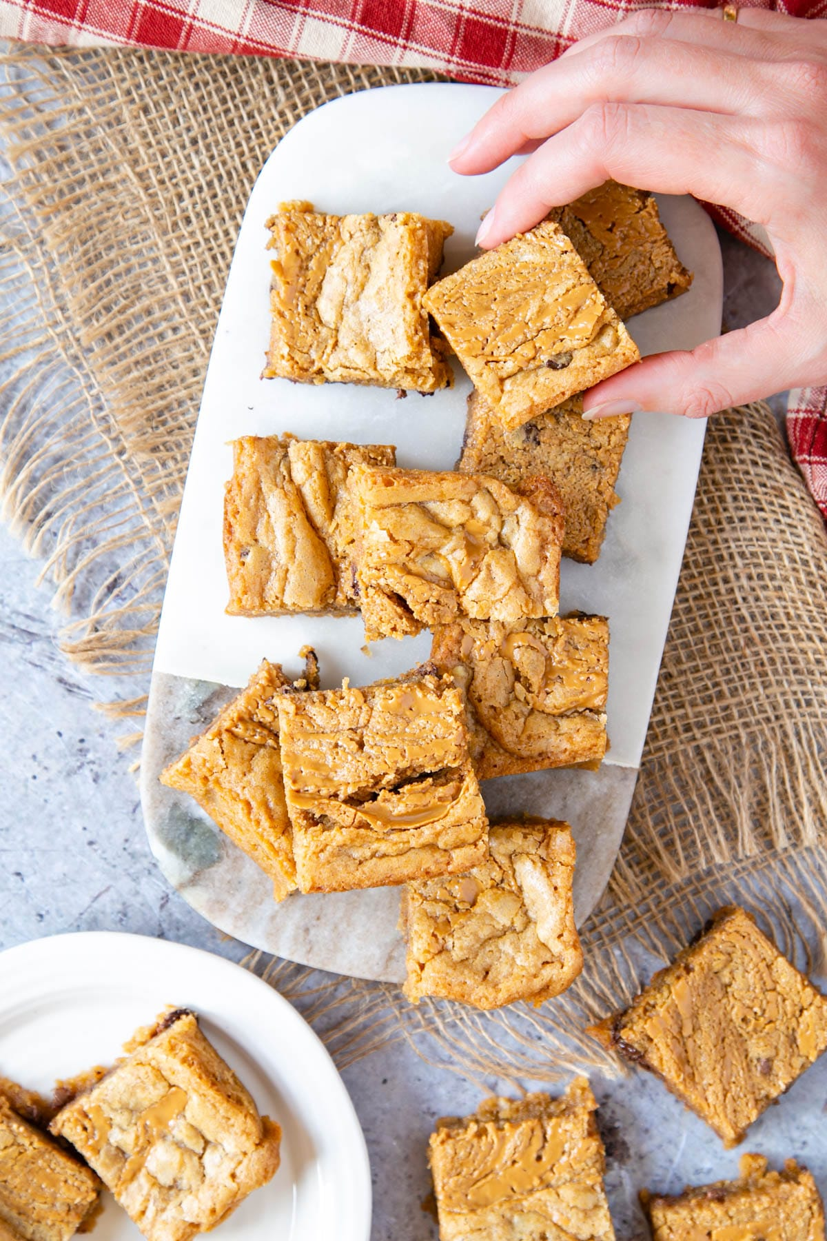 A marble board stacked with peanut butter blondies; a hand has picked one up.