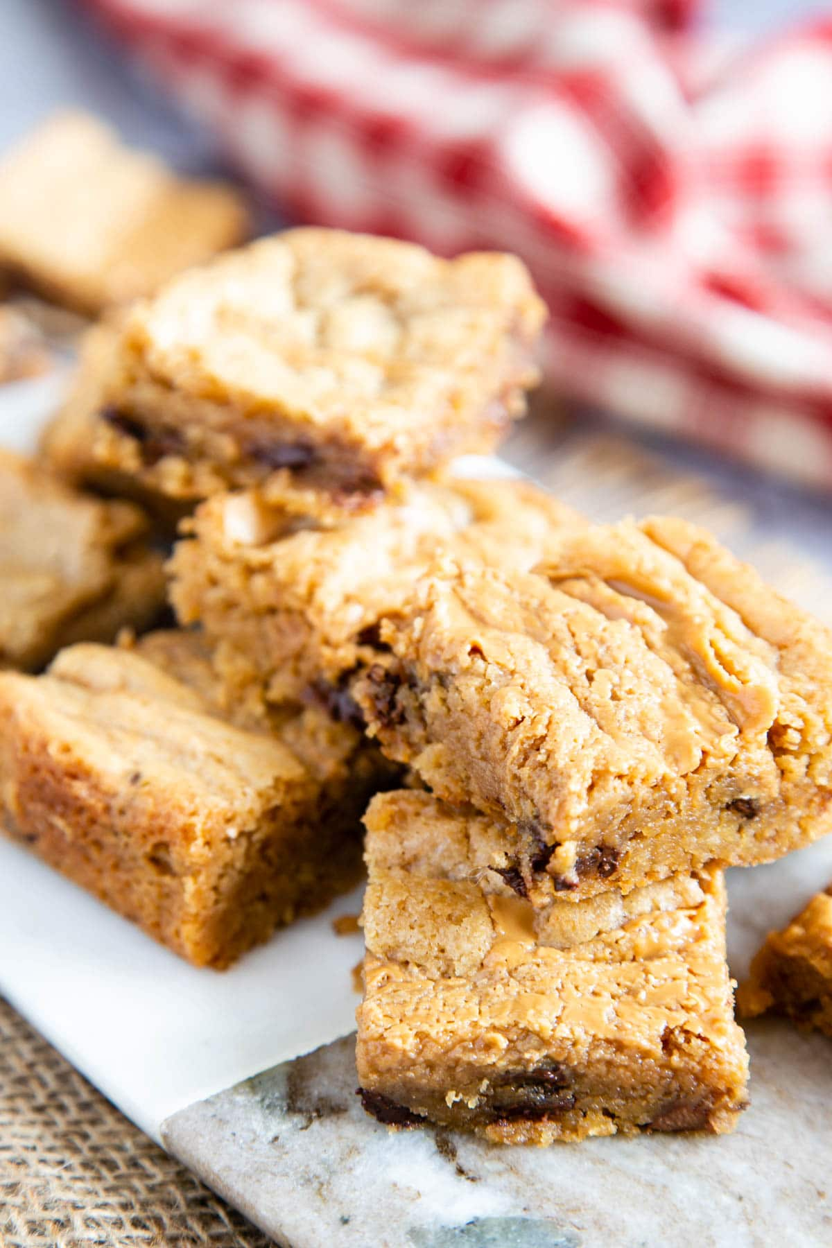 A close up of delicious golden peanut butter blondies stacked two high on a marble board. The chocolate chips can be seen.