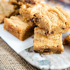 Close up of delicious golden peanut butter blondies, with visible chocolate chips, staked on a board.