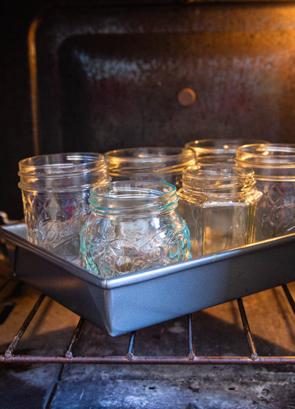 A baking tray of jam jars on a shelf in the oven