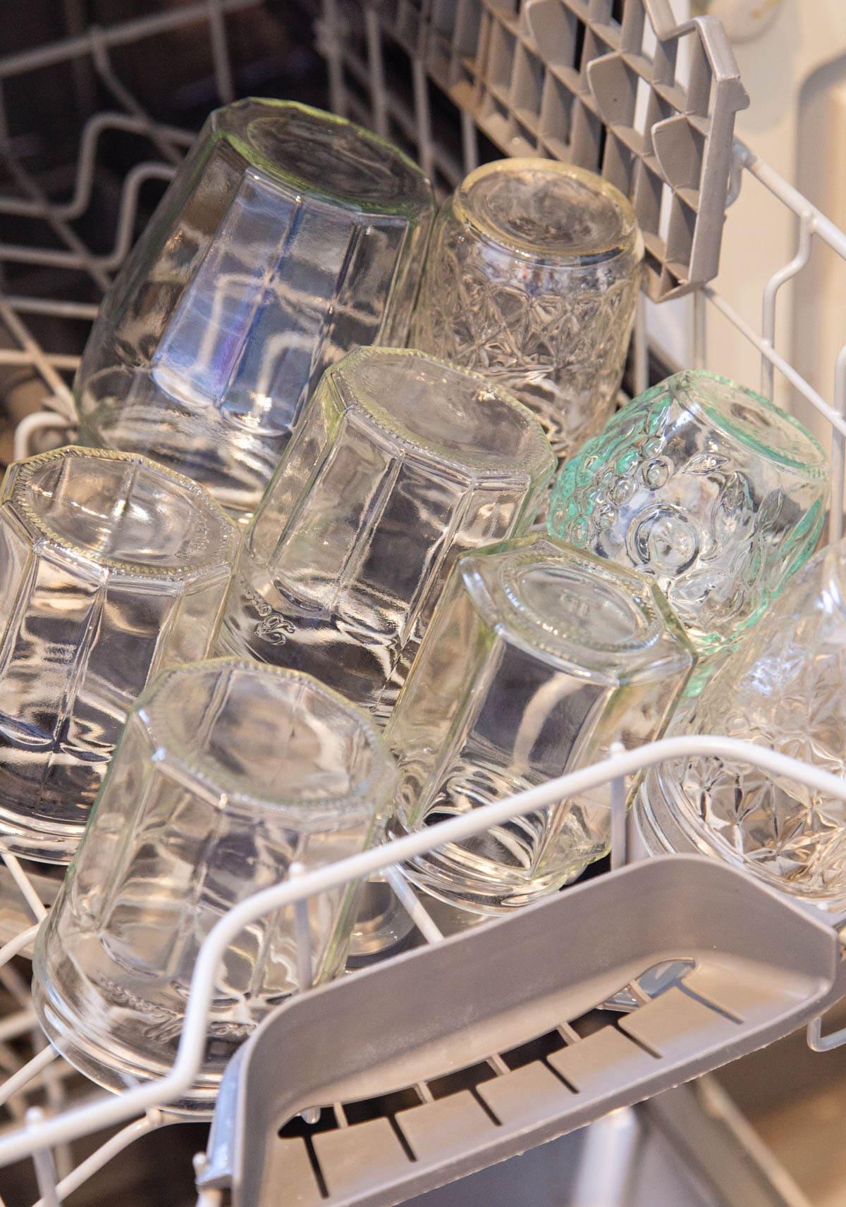 Upside down glass jam jars on the basket on the dishwasher