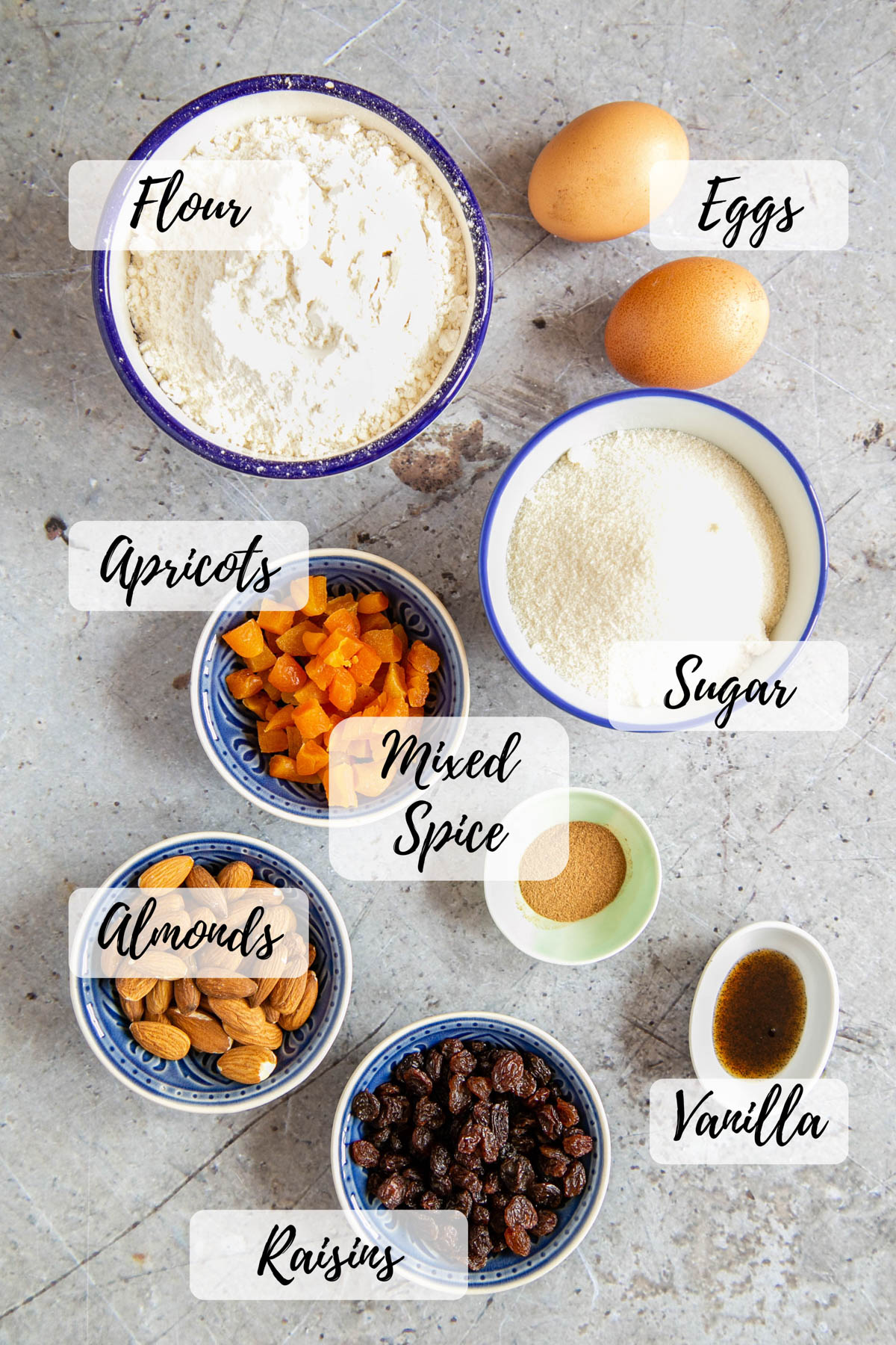 The ingredients for biscotti - flour, eggs, sugar, mixed spice, apricots, raisins, almonds, and vanilla extract. Each ingredient in a small bowl, ready for use.