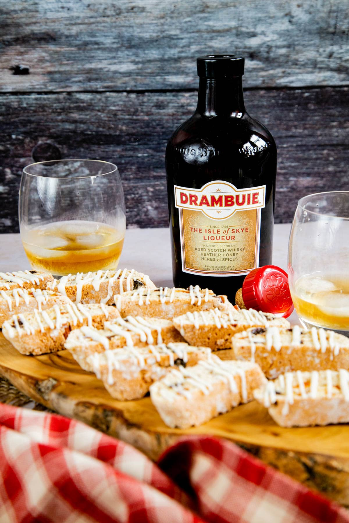 Pieces of Drambuie glazed biscotti on a wooden board, with a bottle and glass of the liqueur standing in the background.