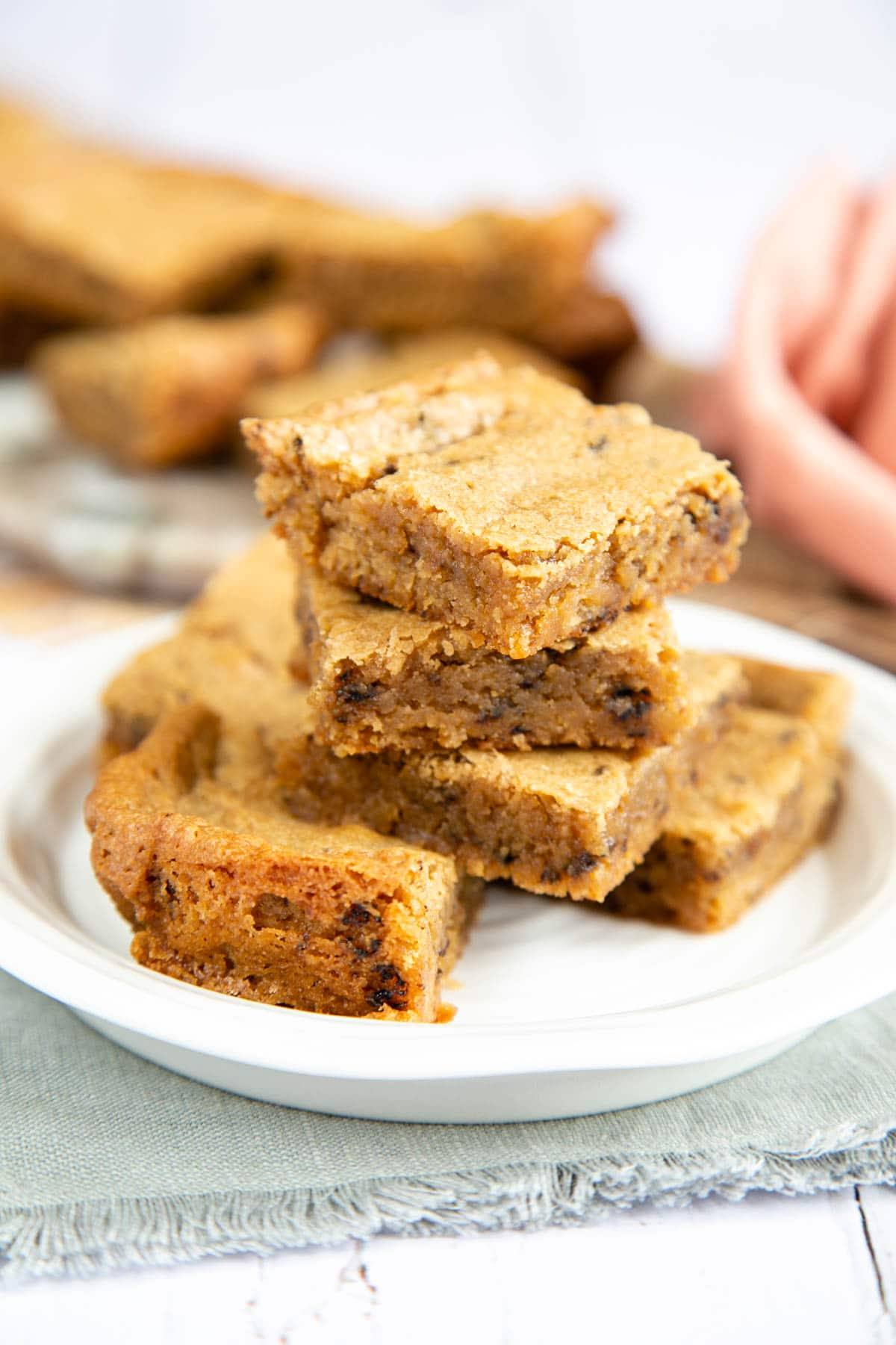 A stack of delicious, rich, crumbly coffee blondies on a small side plate. More blondies are in the background.