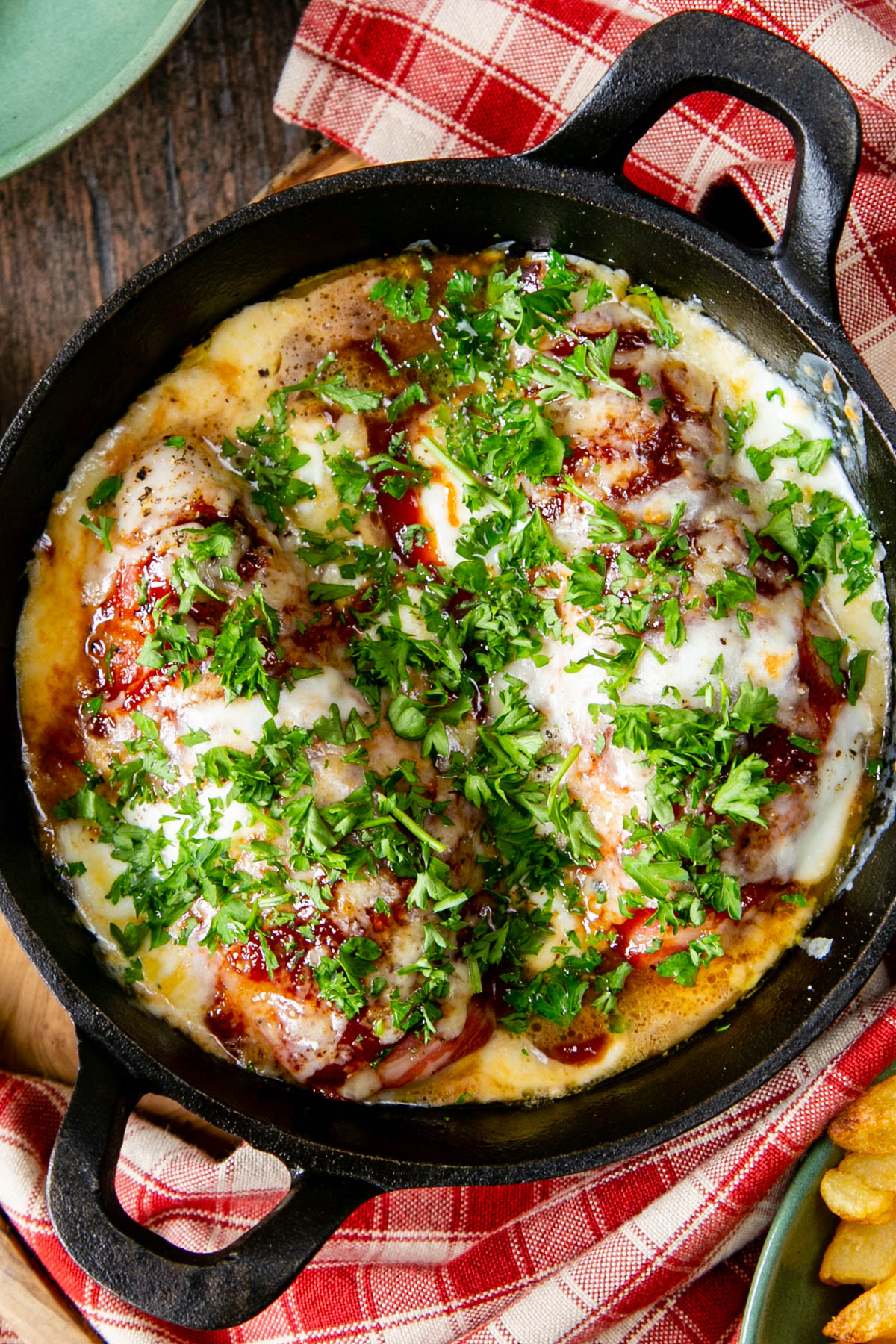 Delicious hunters' chicken for two, oozing with cheese and garnished with green parsley, ready to enjoy. Picture taken from above.