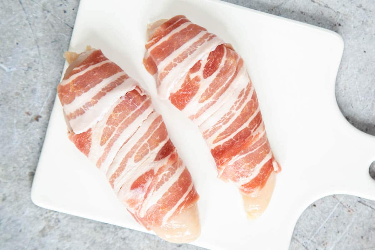 Two chicken breasts wrapped in streaky bacon, on a white porcelain board. The ends of the