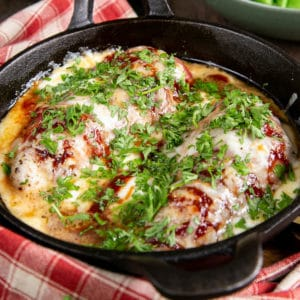 Delicious hunters' chicken: two chicken breasts, wrapped in bacon, coated in BBQ sauce and cheese, garnished with bright green parsley, in close up.