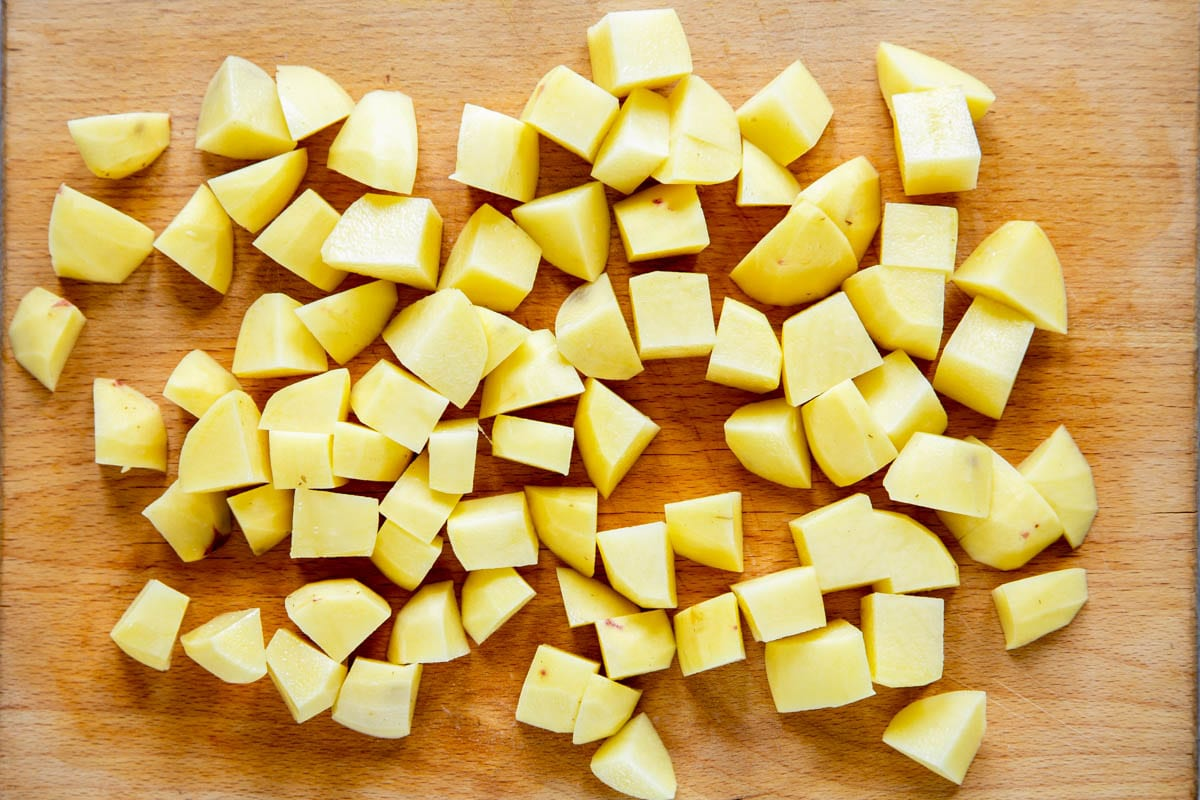 Potatoes, peeled and cubed, on a wooden chopping board.