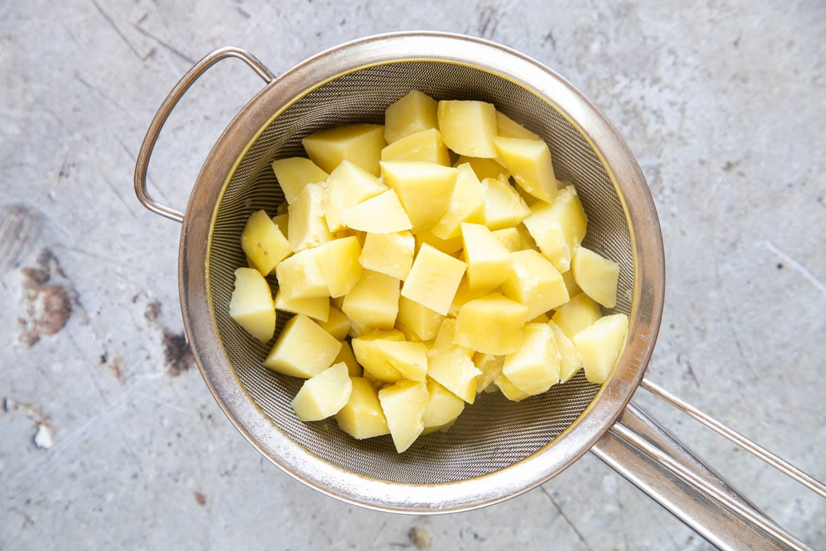 Cubed potatoes after parboiling, in a sieve placed over a saucepan. The potatoes are drying before roasting.