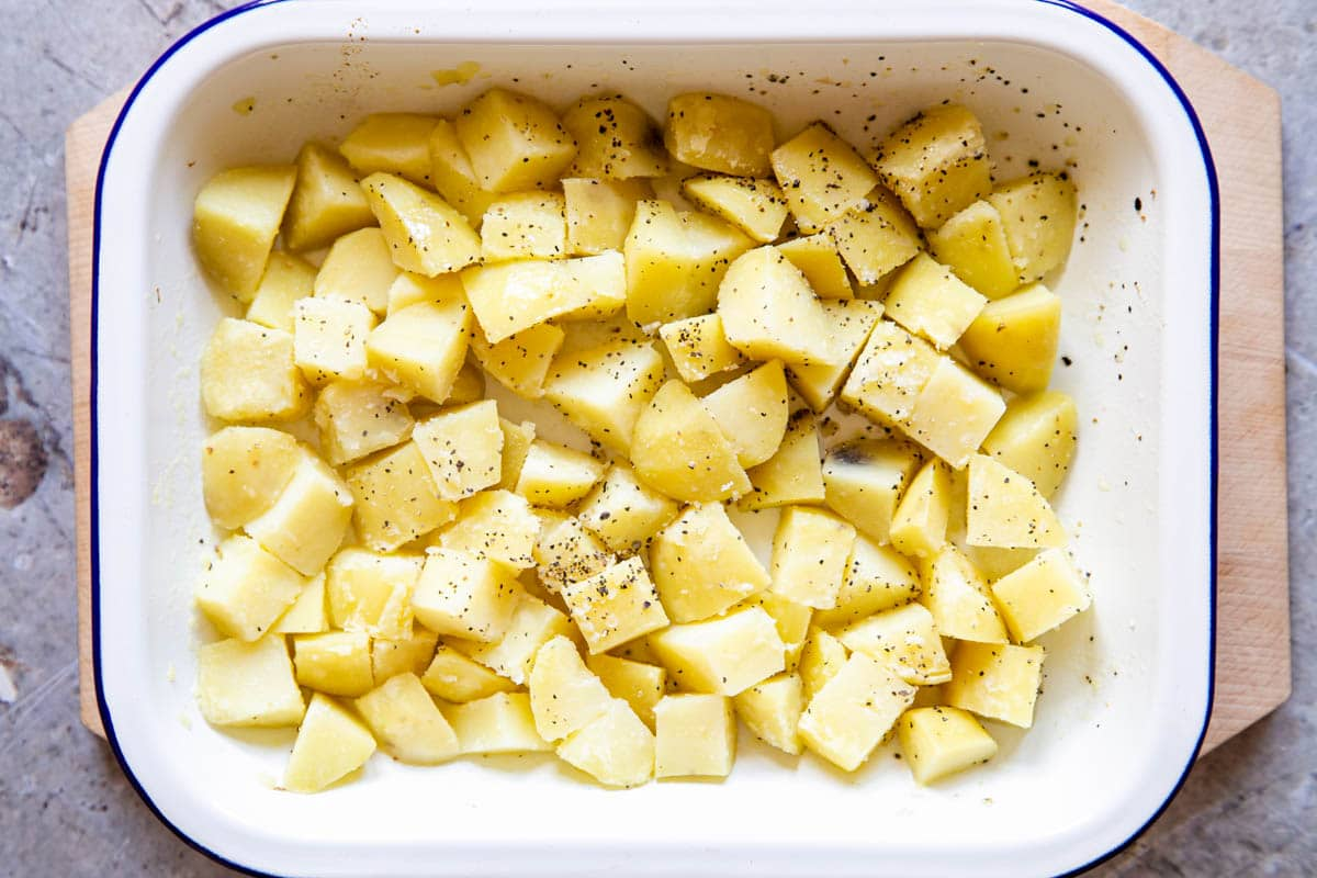 Cubed potato in a white enamel dish. The potato has been seasoned with salt and ground black pepper.