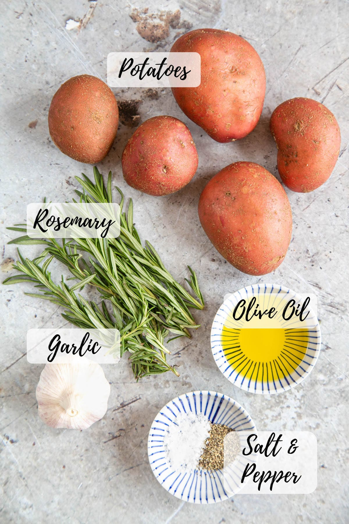 Ingredients for parmentier potatoes - potatoes, rosemary, garlic, olive oil, salt and pepper.