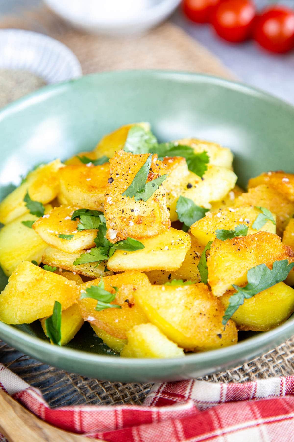 A green ceramic bowl full of golden crispy fried potatoes
