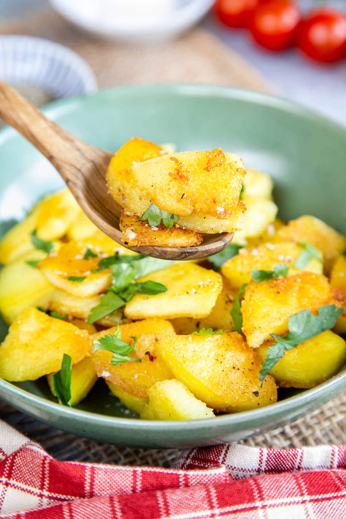 A wooden spoon with a few slices of golden crispy potato held above a green bowl with more potatoes