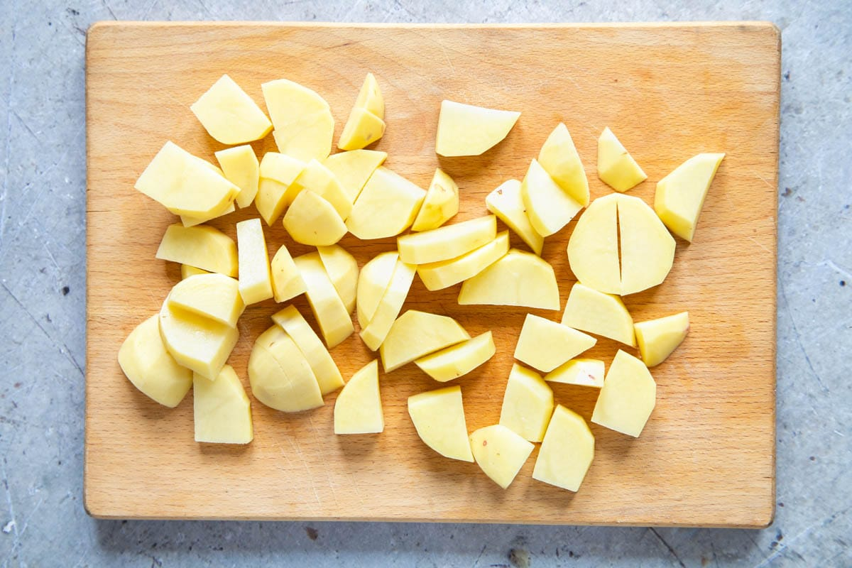 A wooden chopping board with a pile of peeled, chopped potatoes.