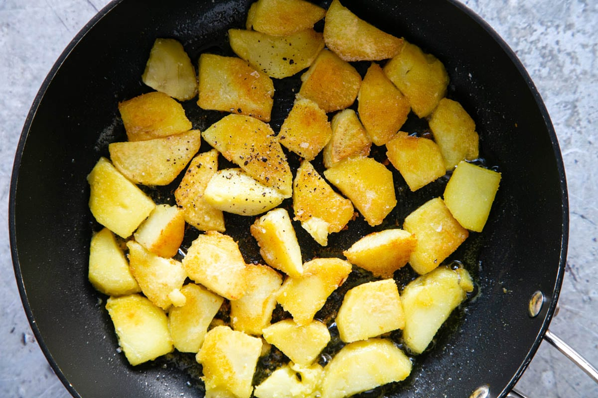 A large frying pan with a single layer of golden brown crispy fried potatoes