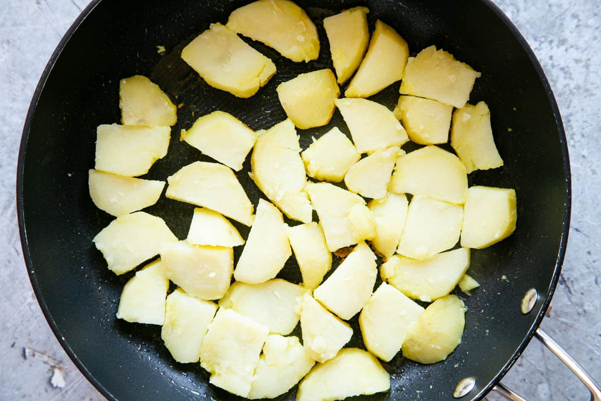 A large frying pan containing a single layer of parboiled potatos
