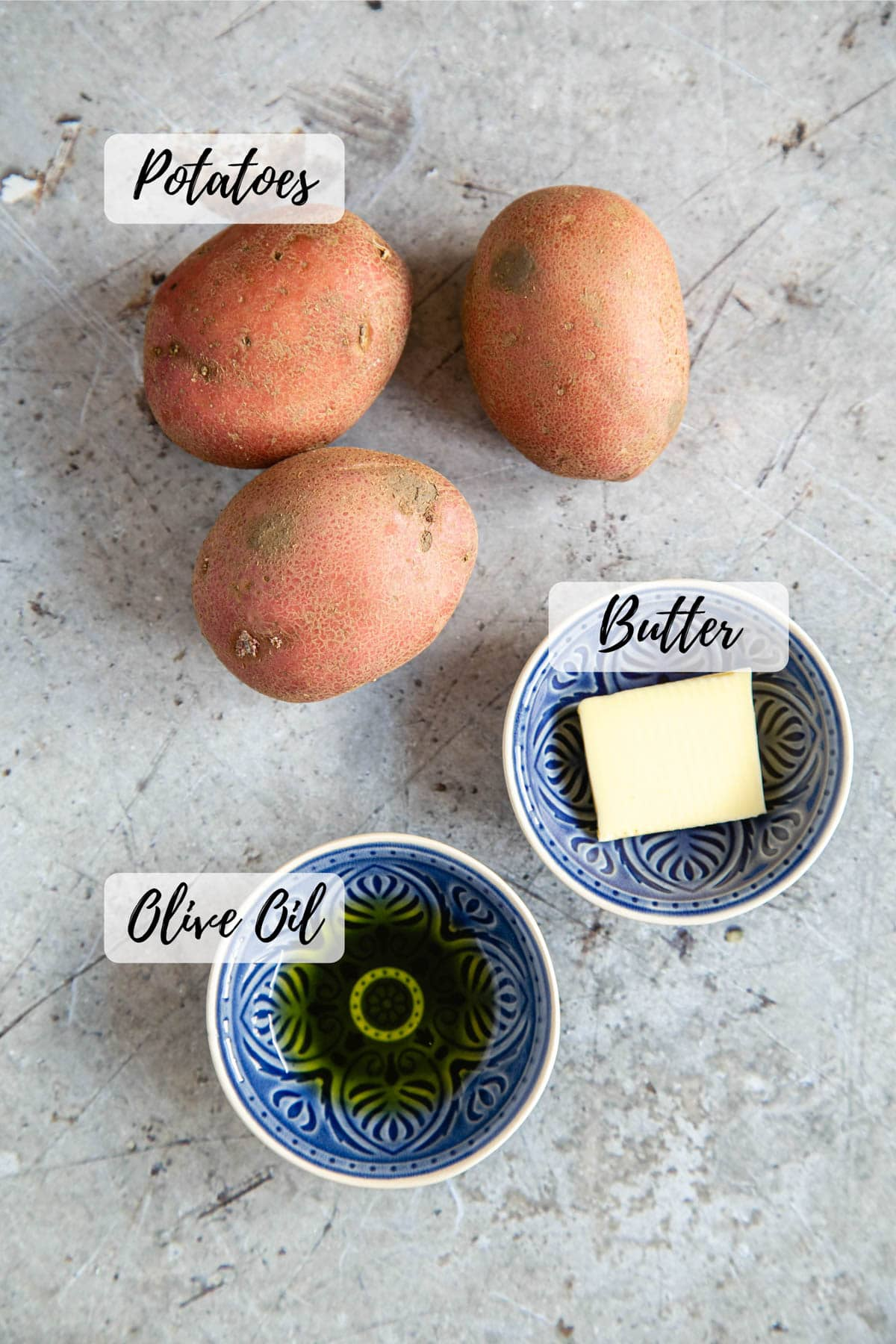 three potatoes two small blue bowls containing olive oil and butter. Text overlay reads olive oil, potatoes and butter
