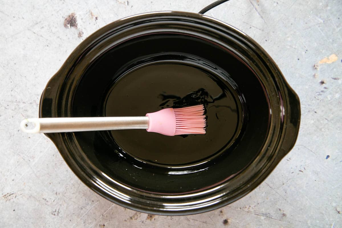 Preparing a slow cooker pot by brushing the inside with cooking oil. A pink silicone brush used to spread the oil sits in the pot. .
