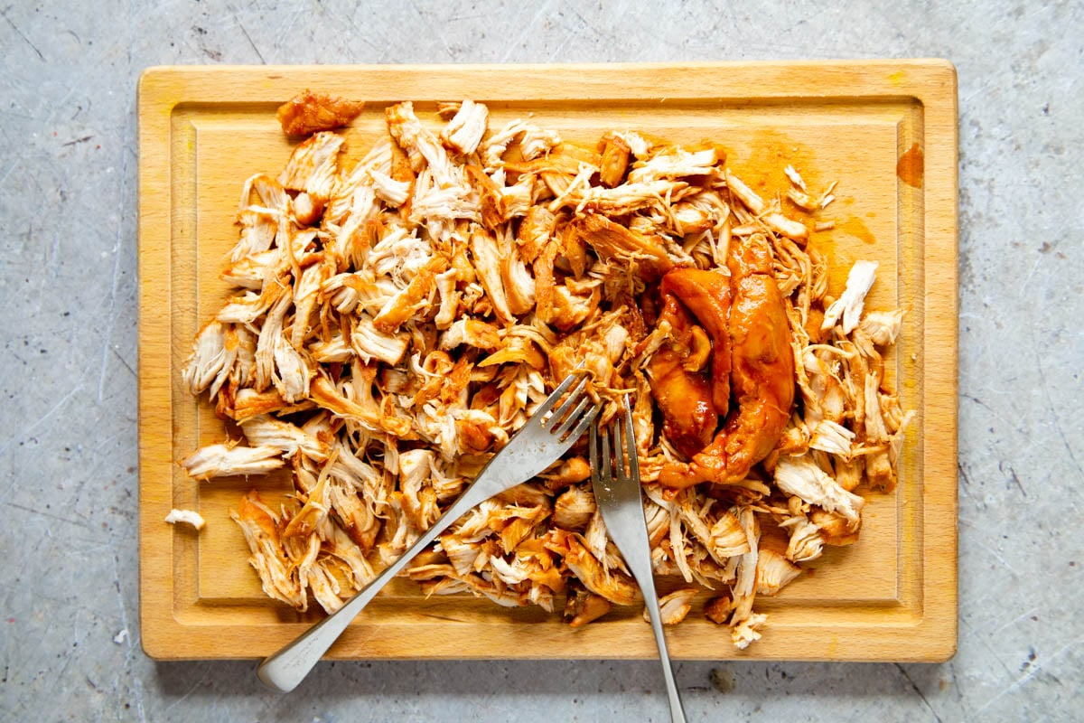 Shredding slow cooked pulled chicken on a wooden board. Two forks, used for shredding, are laid on top of the chicken.