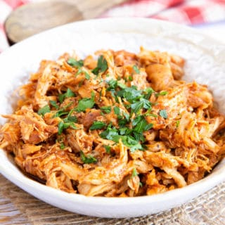 Close up of shredded chicken, garnished with chopped parsley.