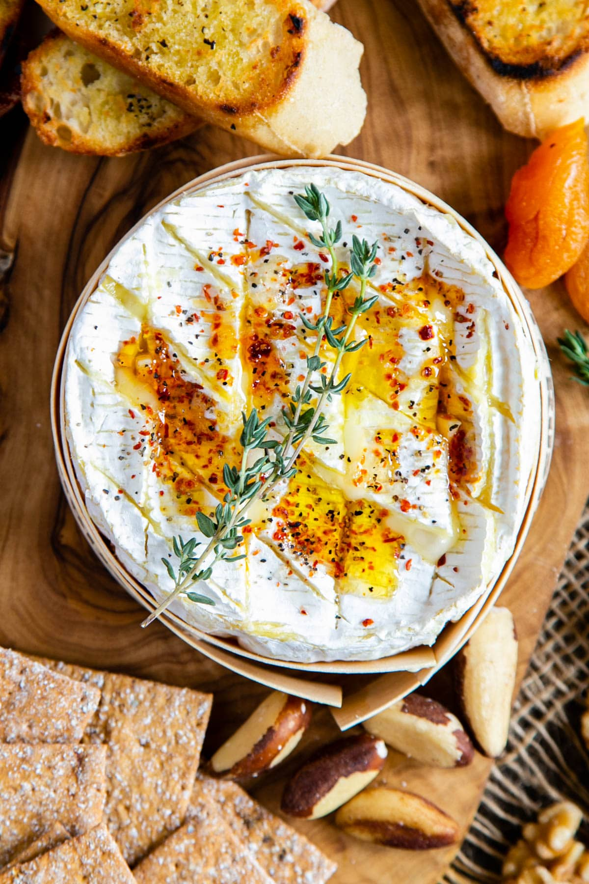 Camembert ready for eating, with suitable accompanyments such as toasted baguette, nuts, crackers and dried apricots.