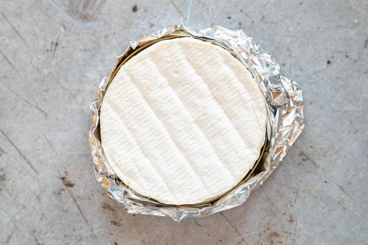 A camembert in its wooden box wrapped in kitchen foil. The wooden lid has been removed, showing the cheese.