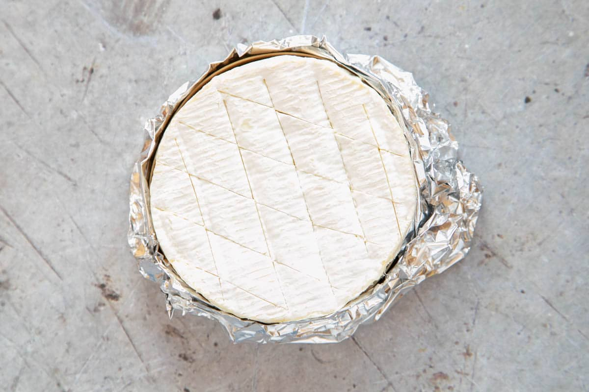 The top of the camembert has been cut through in a shallow cross hatch pattern.