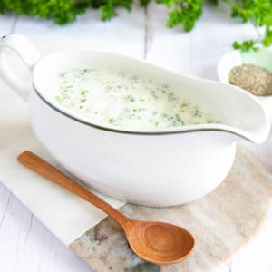 Close up of a white jug filled with white and green parsley sauce.